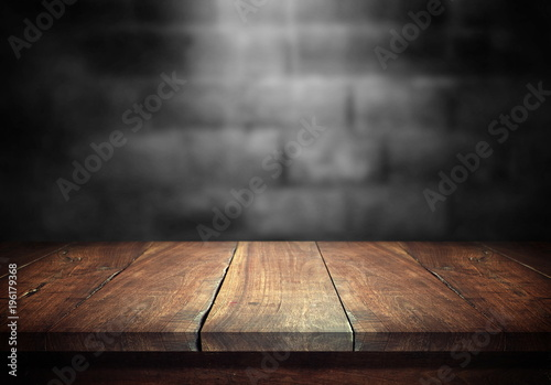 Fotobehang Hout Old wood table with blurred concrete block wall in dark room background.