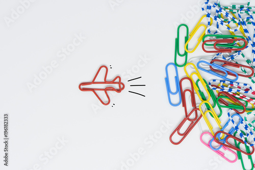Obraz Business concept for group of stacked paperclip with another one red plane paperclip is point to another direction as a team leadership - fototapety do salonu