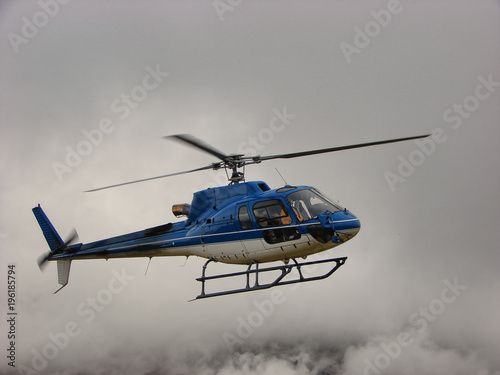 Blue helicopter flying in clouds