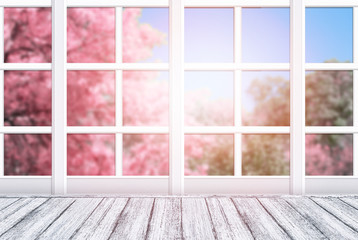 FototapetaRoom interior with window frame and wooden table in Shabby Chic style. Spring sunny day with pink sakura trees outside.