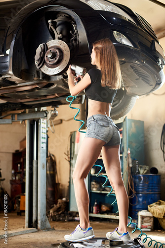 Fotografía  Long legged model repairs the steering mechanism of a lifted in a garage car