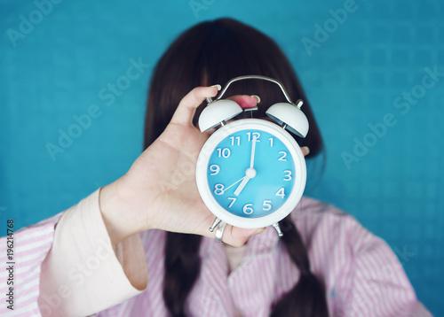 Mujer joven sujetando un reloj retro con sus manos