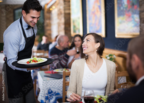Fototapeta waiter man serving company at restaurant