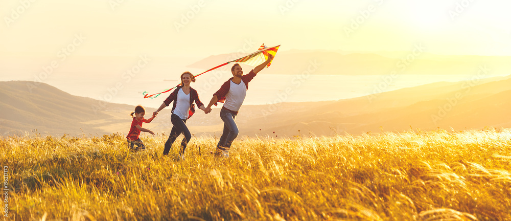 Fototapeta Happy family father,  mother and child daughter launch a kite on nature at sunset