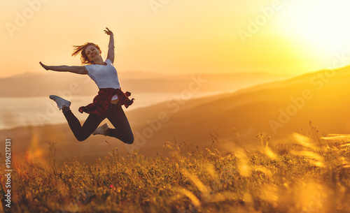 Happy woman jumping and enjoying life  at sunset in mountains. Wallpaper Mural