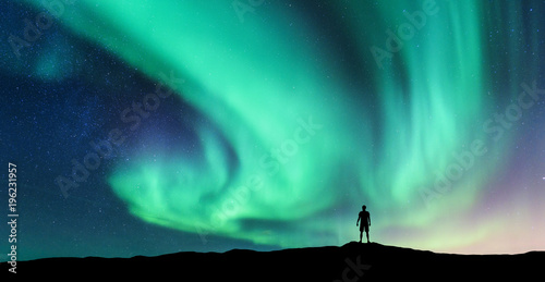 Foto op Aluminium Groene koraal Aurora borealis and silhouette of standing man. Lofoten islands, Norway. Aurora and happy man. Sky with stars and green polar lights. Night landscape with aurora and people. Concept. Nature background