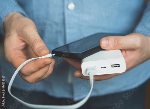 Man charging smartphone with power bank. Canvas Print