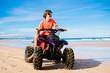 Teenager riding quad bike on beach