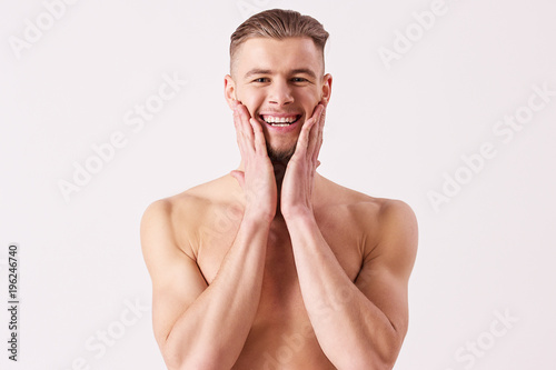 Portrait of young naked man applying aftershave and smiling while standing isolated on white background Wallpaper Mural