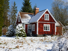 Snow Covered Red Cabin In The Swedish Woods