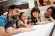 Happy family is relaxing on mattress in orthopedic furniture store. Big family check softness of mattress