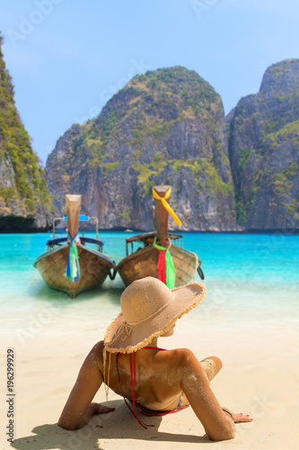 Photo Young woman sitting on the beach at Maya Bay on Phi Phi Leh Island, Krabi Province, Thailand
