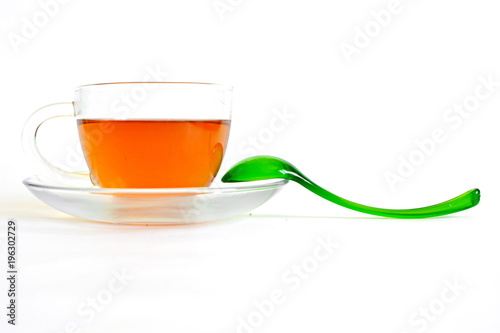 hot black tea in transparent glass cup on saucer with green spoon on white background