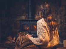 Young Woman With Dog By The Fire