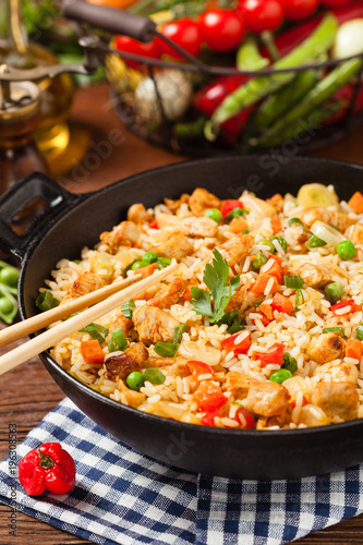 Photo  Fried rice with chicken. Prepared and served in a wok.