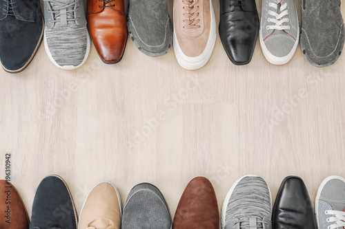 Different male shoes on wooden floor