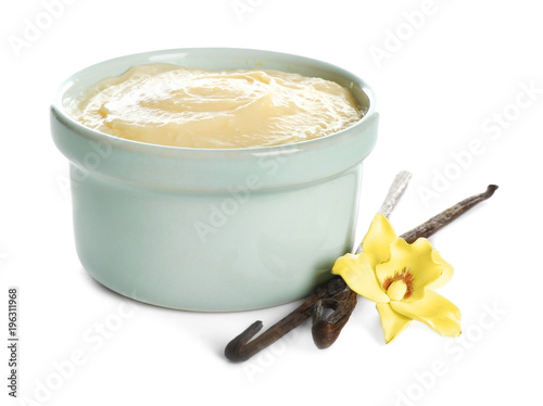 Tasty vanilla pudding in ramekin and sticks with flower on white background Poster Mural XXL