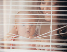 Woman With Child Smile At Window Shutters