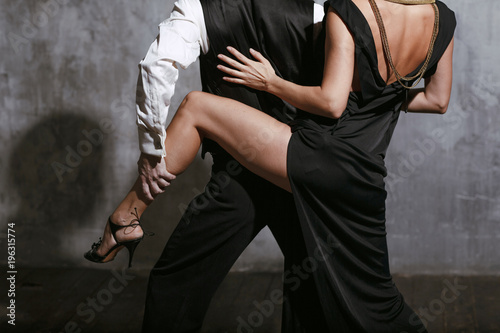 Leinwand Poster Young pretty woman in black dress and man dance tango