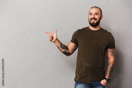 Image of unshaved joyful guy with tattoos on hands posing at camera and pointing Wallpaper Mural