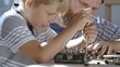 Boy of primary school age trying to repair his toy car and using screwdriver to put its details back in place