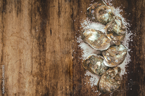 Dozen fresh oysters on the wooden and sea salt. Top view