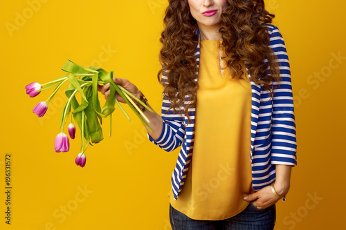 sad young woman on yellow background holding wilted flowers Canvas Print