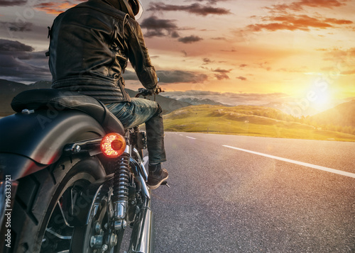 Motorcycle rider ready for drive in Alps, beautiful sunset sky Canvas Print