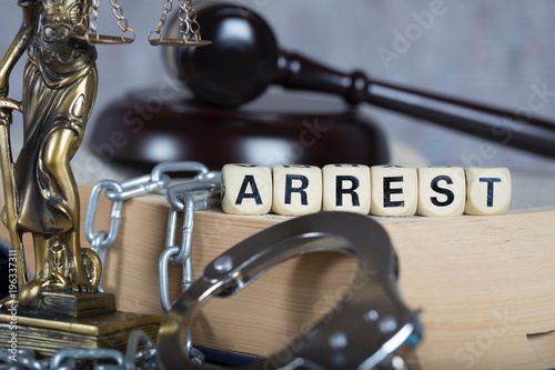 Photo Word ARREST composed of wooden letters.