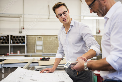 Two businessmen in factory discussing component and plan
