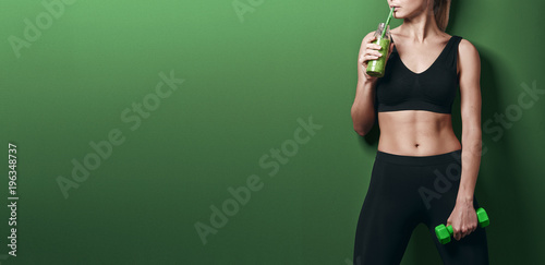 girl with dumbbells and smoothies. concept of healthy nutrition and sport. healthy lifestyle