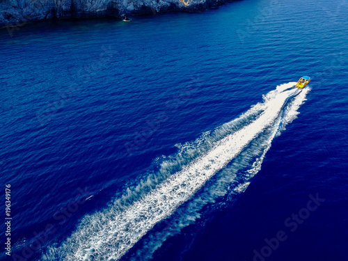 Photo Stands Water Motor sports Bird's eyes view of motor boat sailing on the exotic sea near the seaside.