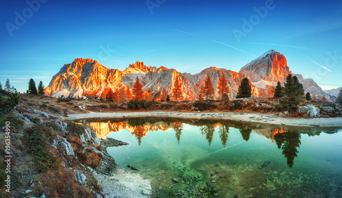 Photo Stands Lake Tofana di Rozes mountain ridge. Region Trentino Alto Adige, South Tyrol, Veneto, Italy. Dolomite Alps, famous travel destination in Europe. Vicinity of village Cortina D'Ampezzo and lake Limides.