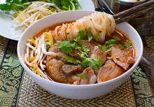 Asian Spicy Noodle Soup With Chopstick Hold On Noodle With Pork Bone And Fresh Vegetable On Bamboo Wicker Thai  Style, Home Made, Hot And Spicy Noodle Soup, Asian Food.