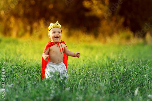 Little boy prince,child king laughing summer day outdoors around colorful green grass.Funny knight baby 1-2 years.Cute kid smile dressed image playing hero,knight,warrior,red cloak,gold crown.