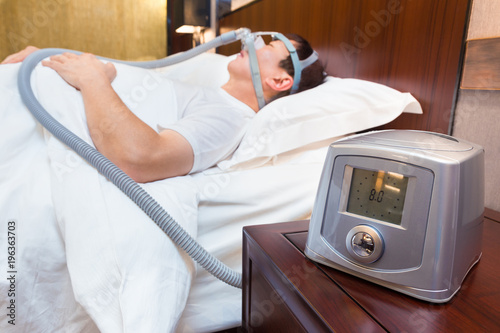 CPAP machine sitting on a bedside table with blurred Middle age asian man sleepi Canvas Print