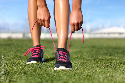 Láminas  Running and fitness exercise sport girl getting ready tying shoes jogging on park grass