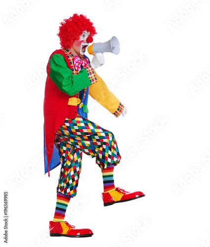 Side view full length picture of a walking clown screaming into loudspeaker