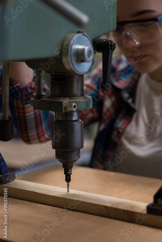 Female carpenter using vertical drill machine