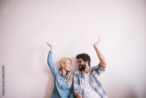 Fotografia  Happy charming young love couple looking each other and with raised arms holding the empty space above while sitting on the floor