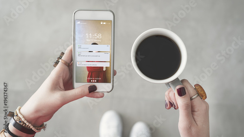 Woman holding mobile phone and reading messages from screen other hand holding coffee cup