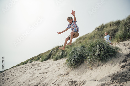Little Boy Jumping Over a Sand Dune Fotobehang