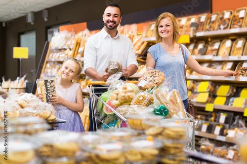 Deurstickers Bakkerij Portrait of family choosing bread and sweets in bakery section