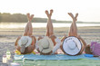 Three girls laying on the sandy beach with legs up