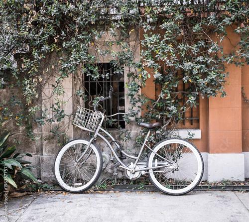 Deurstickers Fiets locked bicycle against wall. vintage locked bike with basket in city.