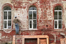 Working Restorer Restores The Old Wall Of The Building. Texture Of Old Brick Wall.