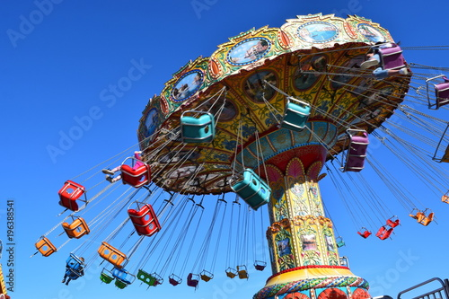 Colorful carnival ride at amusement park, summer day.
