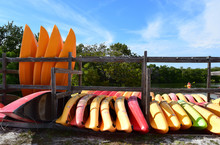 Group Of Orange Kayaks On Shor...