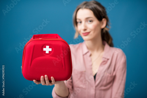Fotografie, Tablou Portrait of a woman with first aid kit on the blue wall background