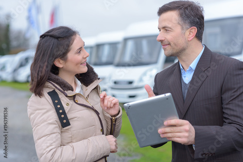 Vehicle salesman holding touchscreen tablet
